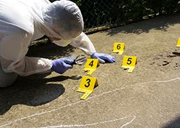 Crime scene investigator peering through magnifying glass at evidence